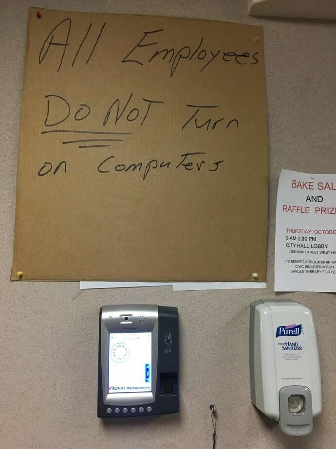 A hand-lettered sign on a corrugated box panel hung above a time clock on the 2nd floor of West Haven City Hall cautions employees not to turn on their computers while the effects of a cyber attack are mitigated.