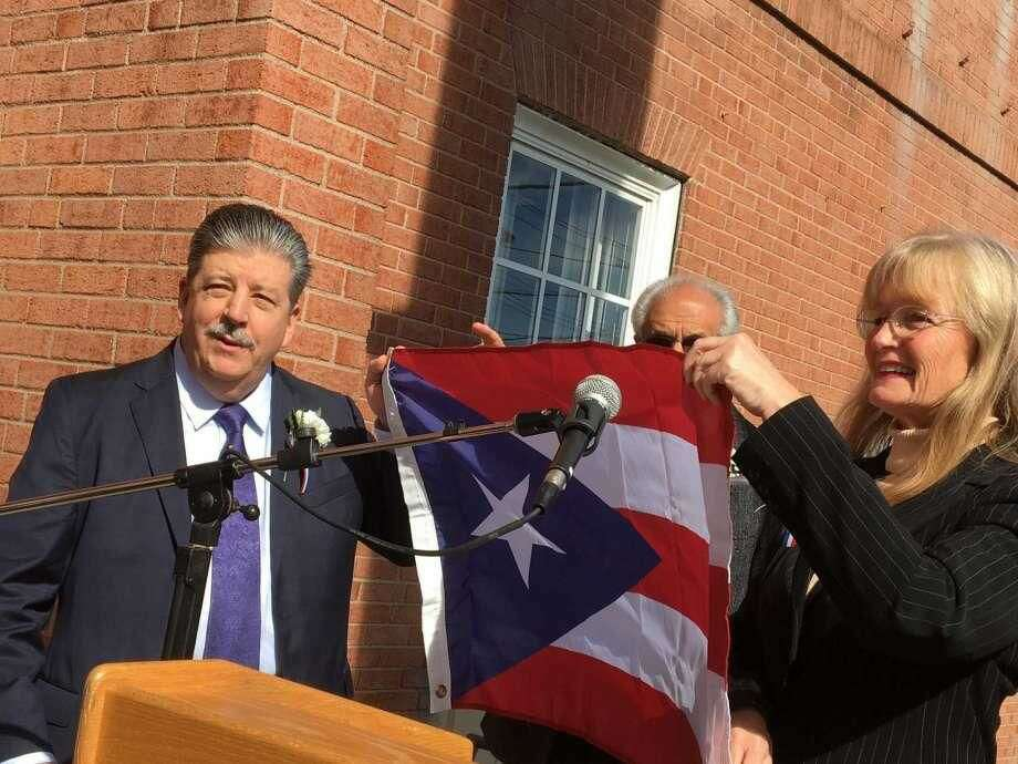 West Haven honored veterinarian Dr. Ralph Padilla on Friday, Oct. 19, as its first-ever Hispanic American of the Year. Mayor Nancy Rossi, right, presented Padilla, left, with the flag of Puerto Rico, as Master of Ceremonies Louis Esposito, Rossi's executive assistant, looks on.