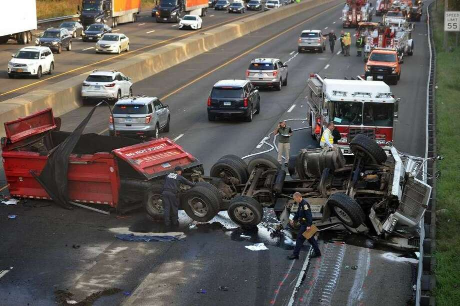 Police investigate the scene of a fatal truck accident that shut down traffic on northbound I-95 north of exit 40 in Milford on Thursday, Nov. 1. The truck had its bed raised and struck the Quarry Road overpass.