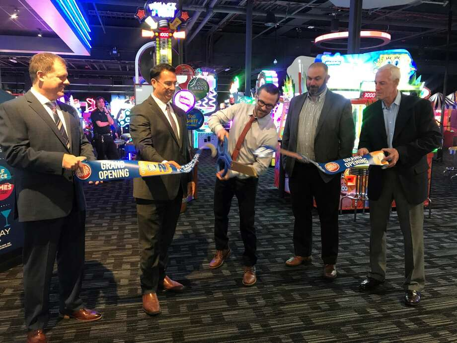 From left, Ken Sterba,  general manager of the Connecticut  Post Mall;  Mayor Ben Blake; William Painter,  general manager, Dave & Busters Milford; Bruce Crane, regional operations manager; and Gary Mullin, executive director of the Milford Chamber of Commerce celebrate Dave & Busters grand opening with an official ribbon cutting.