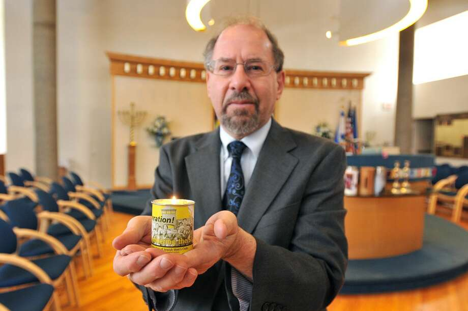 Rabbi Alvin Wainhaus of the Or Shalom synagogue holds a Holocaust Remembrance candle.