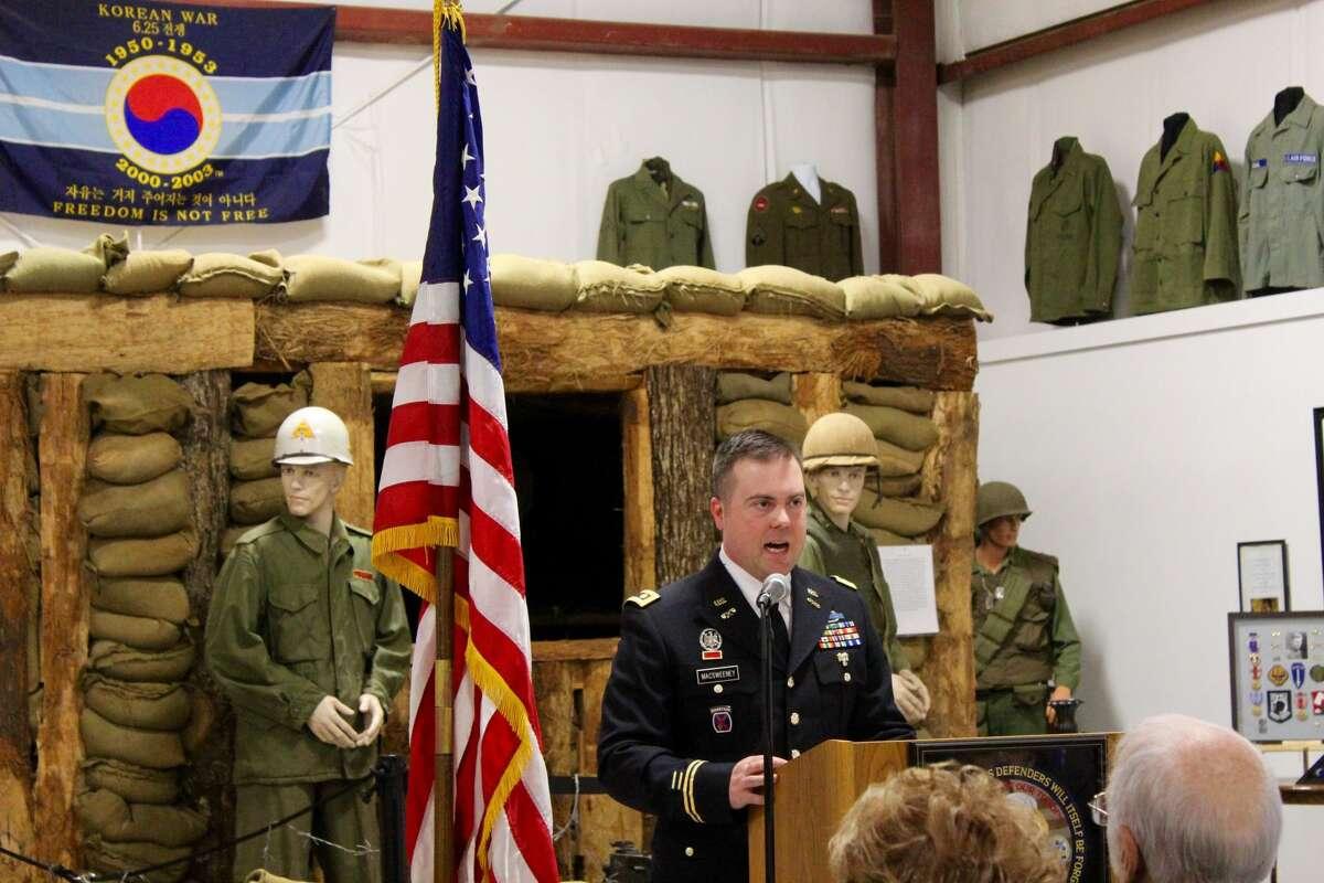 Major Stephen McSweeney addresses the crowd in front of the Korean War display.