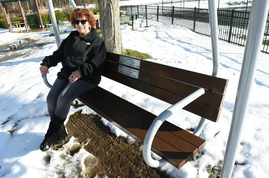 Former Milford animal control officer Pat Liptak sits on a memorial bench swing honoring her deceased daughter, Paige L. Liptak, at Bodie's Place playground in Eisenhower Park in Milford.