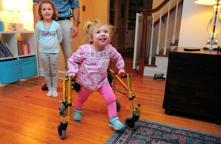 Serena Zitnay, 3, uses her walker to get around as her older sister Emma, 5, looks on while at home in Orange. The family has decided to raise money to try and have a walker made that is more kid friendly.