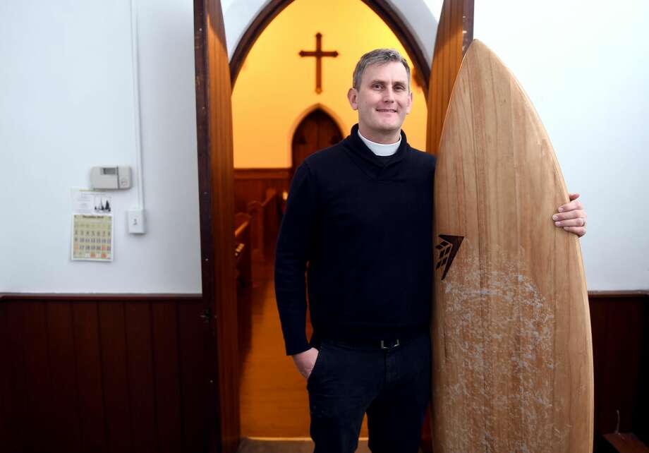 Rev. Matt Lindeman with one of his surfboards at St. Peter's Episcopal Church in Milford.