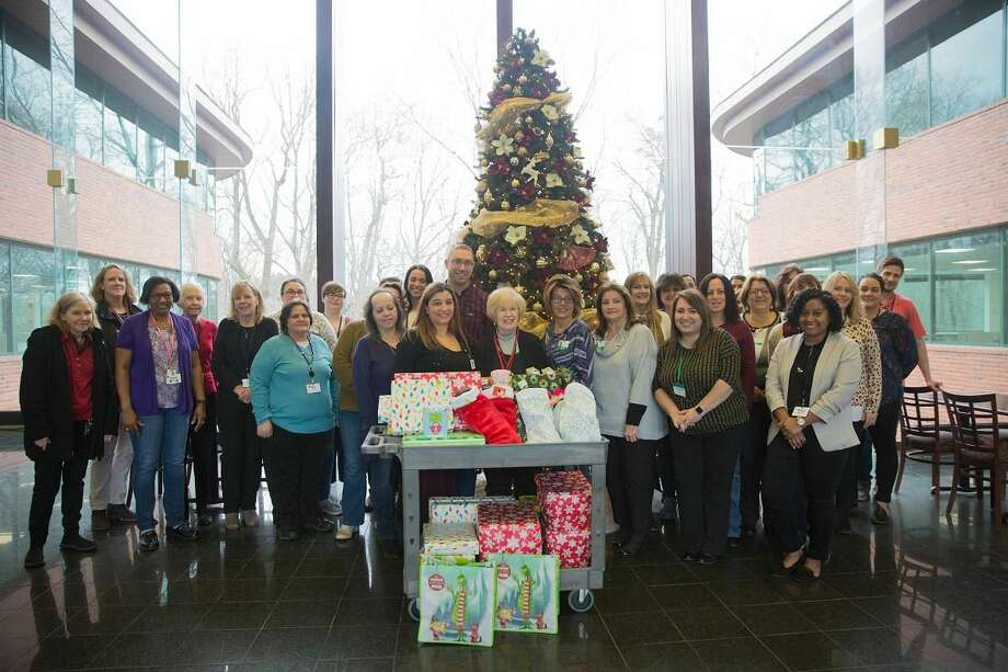Milford Family Resource Center Manager Peggy Kelly, center, with Subway HQ employees who participated in the Adopt-a-Family program on Dec. 17.