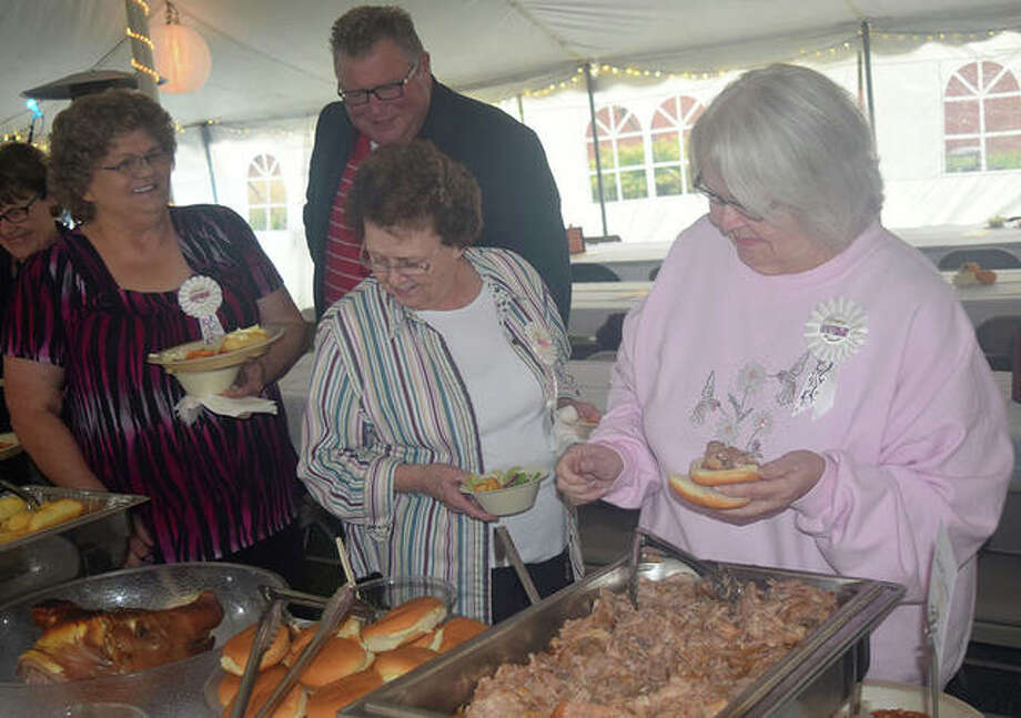 Teresa Francis of Jacksonville (from left), Mayor Andy Ezard, Norma's North Star Cafe owner Norma Koyne and Nancy Randall of Jacksonville get food during Jacksonville Main Street's 20th anniversary celebration Thursday. Photo: Marco Cartolano | Journal-Courier