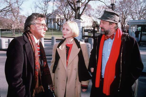 """FILE--Dustin Hoffman, left, Anne Heche, center, and Robert DeNiro, right, are shown in character from the movie """"Wag The Dog"""" in this undated file photo. While idling outside the estate where the Clintons were vacationing Thursday, Aug. 20. 1998, in Martha's Vineyard, the White House press pool was viewing the movie """"Wag The Dog"""" when the military strikes against Sudan and Afghanistan got under way. Coincidently, ``Wag the Dog"""" scripts a foreign crisis to distract attention from the president's sex scandal. (AP Photo/New Line Cinema)"""