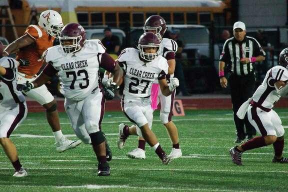 Clear Creek's Rayfield Conley (27) picks his way through the Alvin defense Thursday at Alvin High School.