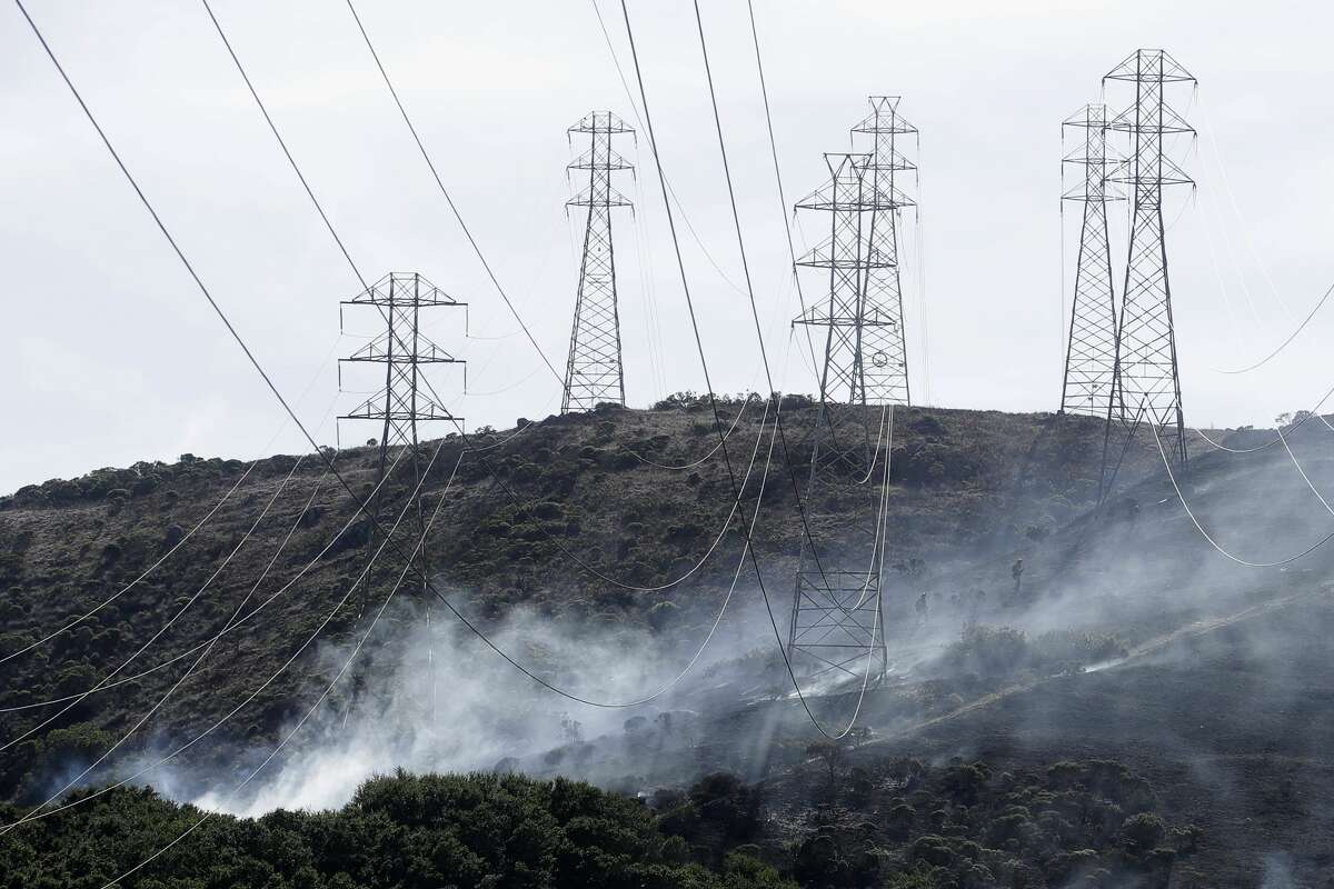 A fire crew works near power lines and electrical towers at a fire on San Bruno Mountain near Brisbane, Calif., Thursday, Oct. 10, 2019. (AP Photo/Jeff Chiu)