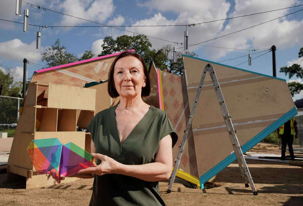 """Artist Marta Chilindrón holds a maquette of """"Mobius Houston"""" as the new monumental sculpture is installed behind her at Wilhelmina's Grove on the Univ. of Houston central campus."""