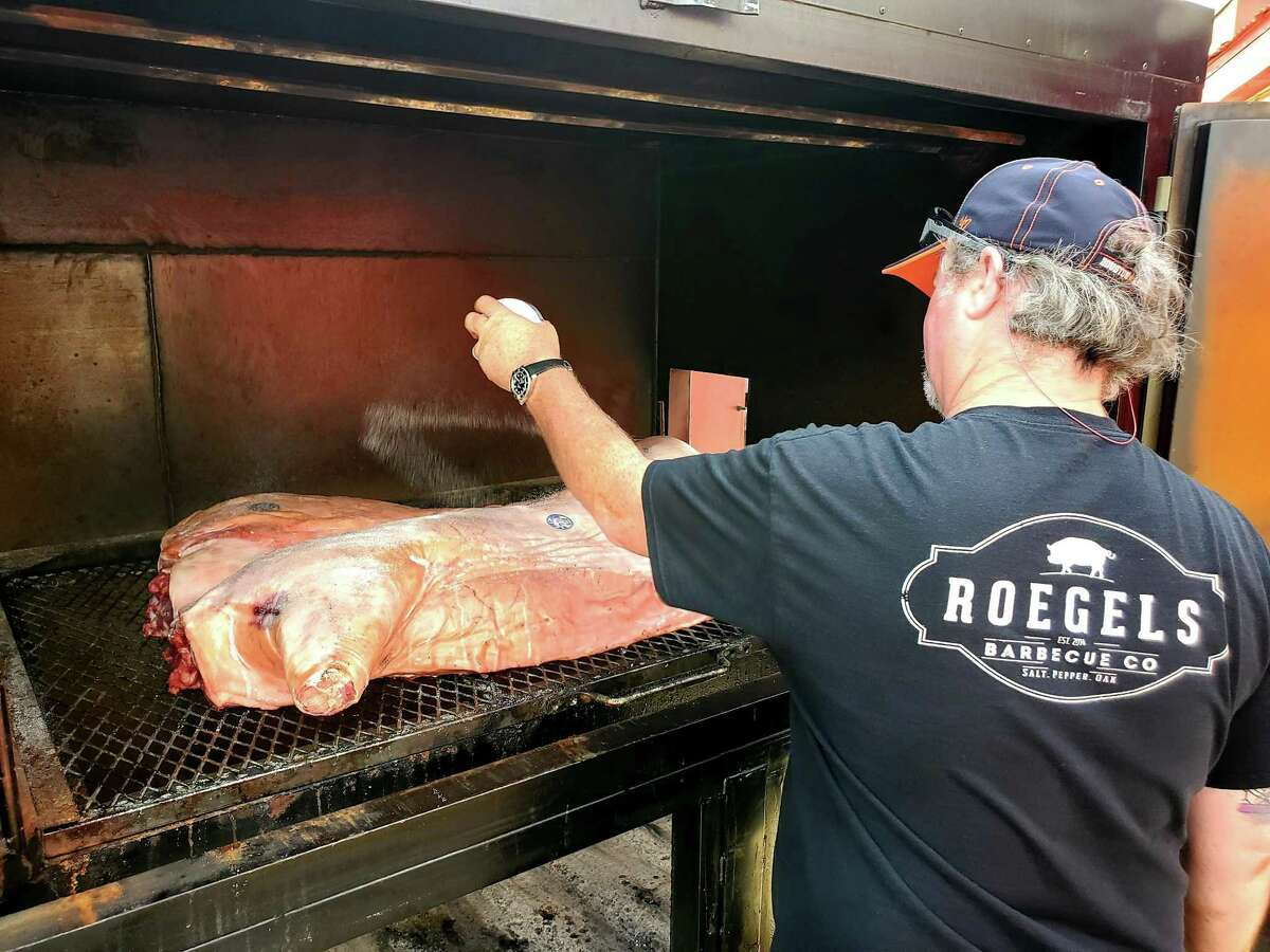 Russell Roegels salts a hog at Roegels Barbecue Co.