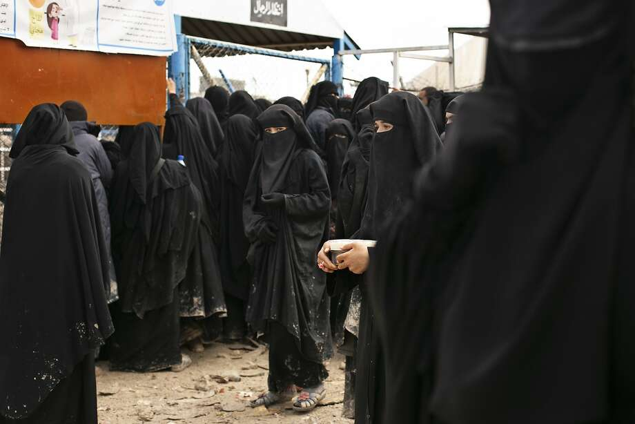 Women line up for aid supplies at al-Hol camp in Syria, some 30 miles from the Turkish border. Photo: Maya Alleruzzo / Associated Press