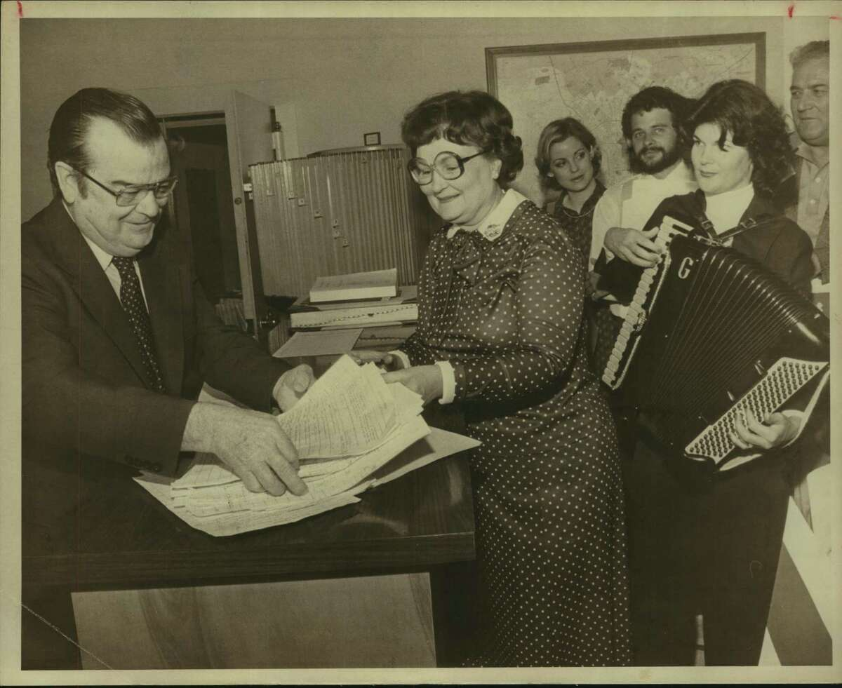 In this undated photograph, Garland Jackson, the city clerk, left, is shown with San Antonio Mayor Lila Cockrell and her daughter Carol Gulley, playing accordian.