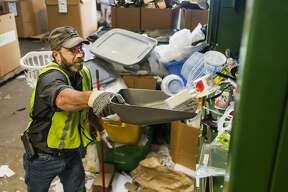 Jason Kempf shovels plastic items into a baler at Midland Recyclers Thursday, Oct. 10, 2019 at the Midland City Landfill. (Katy Kildee/kkildee@mdn.net)