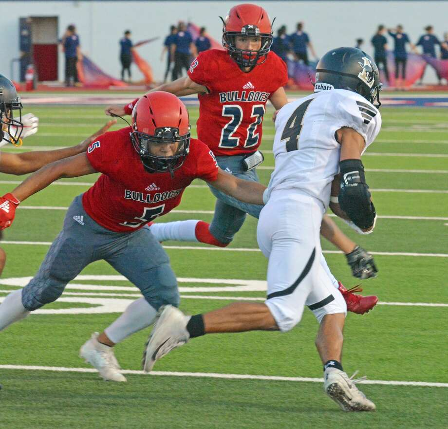 Plainview's Jaidyn Luera (5) and Michael Rhoades (22) try to bring down a Lubbock ball carrier during their non-district football game earlier this season. Luera, Rhoades and the Bulldog defense will be tested greatly against #6 Lubbock Cooper in their District 2-5A opener. Photo: Nathan Giese/Planview Herald