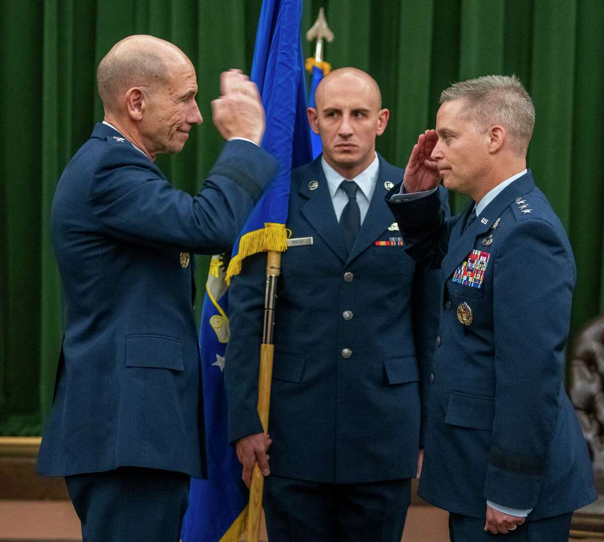 Gen. Mike Holmes, commander of the Air Combat Command , left, salutes newly-promoted Lt. Gen. Timothy D. Haugh at a ceremony Friday at Joint Base San Antonio-Lackland to furl the flags of the 24th and 25th air forces, which are now combined in the new 16th Air Force in charge of intelligence and cyberwarfare.