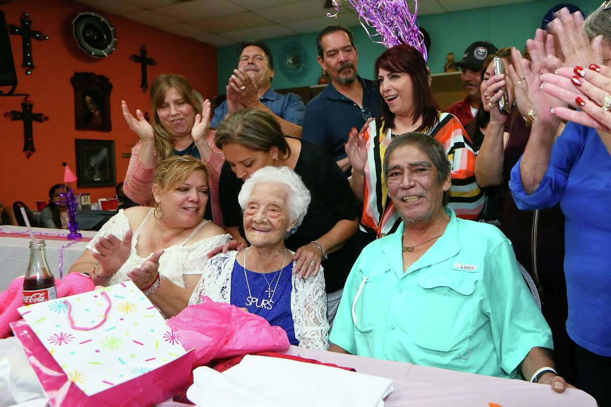 """Family members clap after singing """"Happy Birthday"""" to Ofelia Gonzales, center front, while celebrating her 109th birthday at Arizona Cafe, 1111 S. General McMullen Dr., on Thursday, Oct. 10, 2019. Gonzales is one of approximately 70,000 centenarians living in the United States."""