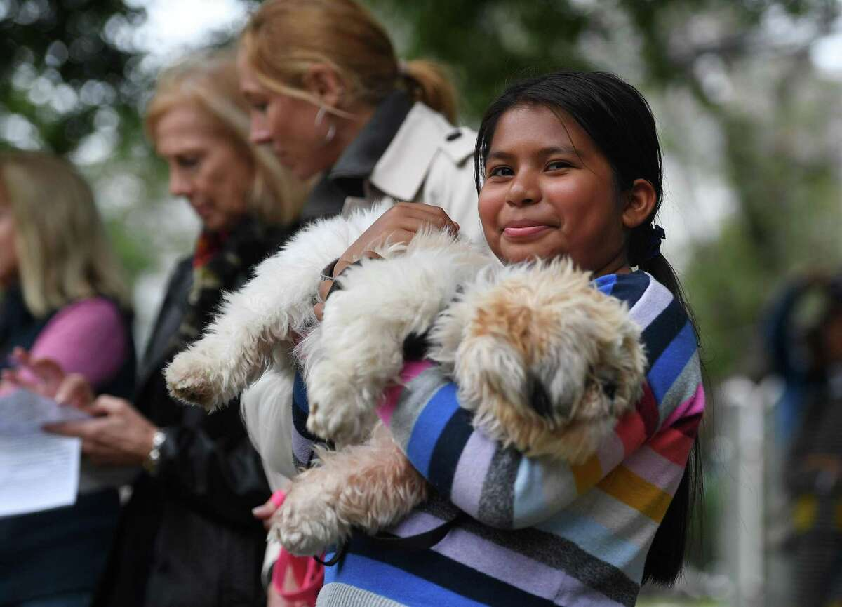 Eisabella Rojas-Huesca, 11, of Westport, holds Benji, her shih tzu, at the annual Blessing of the Animals service at Trinity Episcopal Church in Southport on Sunday, Oct. 6.