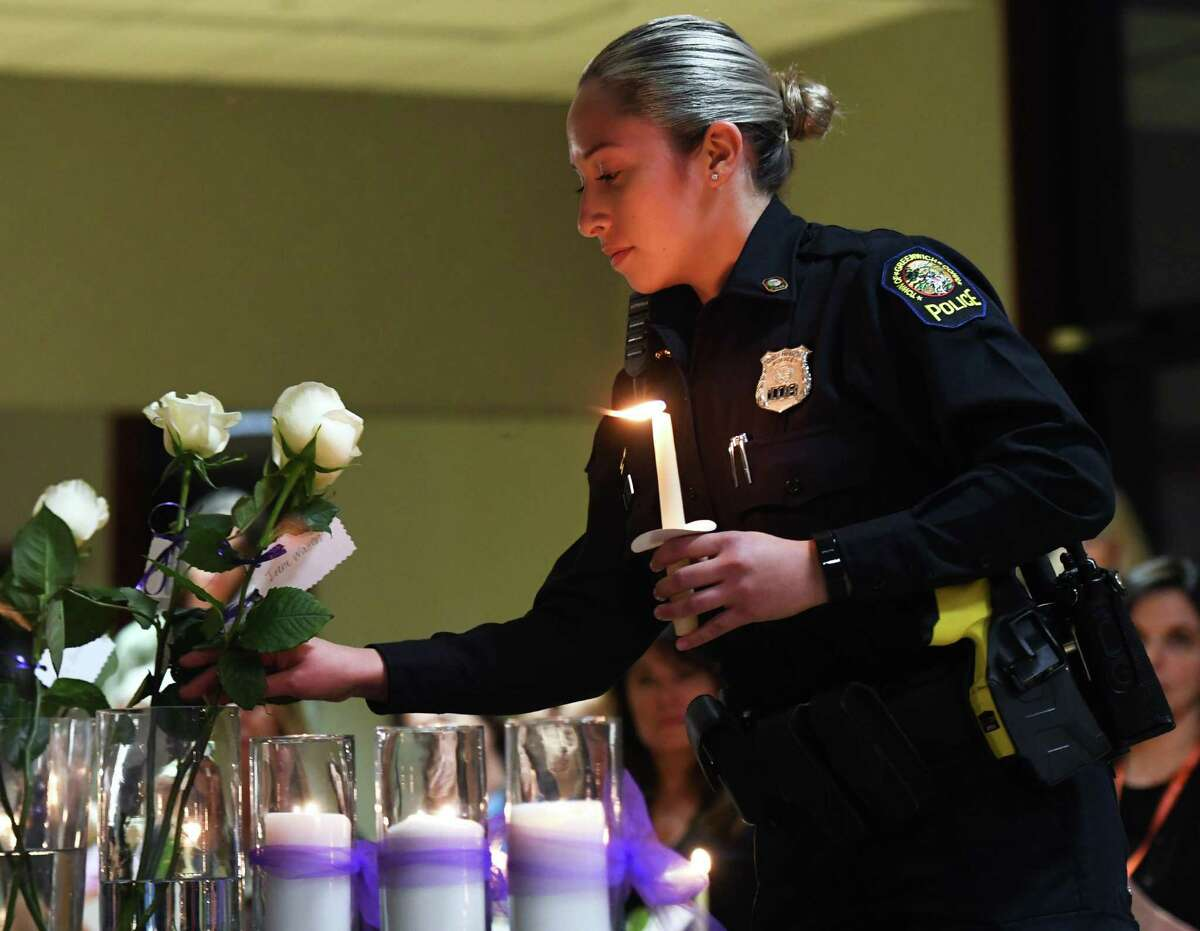 Greenwich Police Officer Sabrina Diaz holds a candle while placing a rose for a victim of domestic violence at the annual Domestic Violence Candlelight Vigil and Art Show Reception at the YWCA in Greenwich, Conn. Thursday, Oct. 10, 2019.
