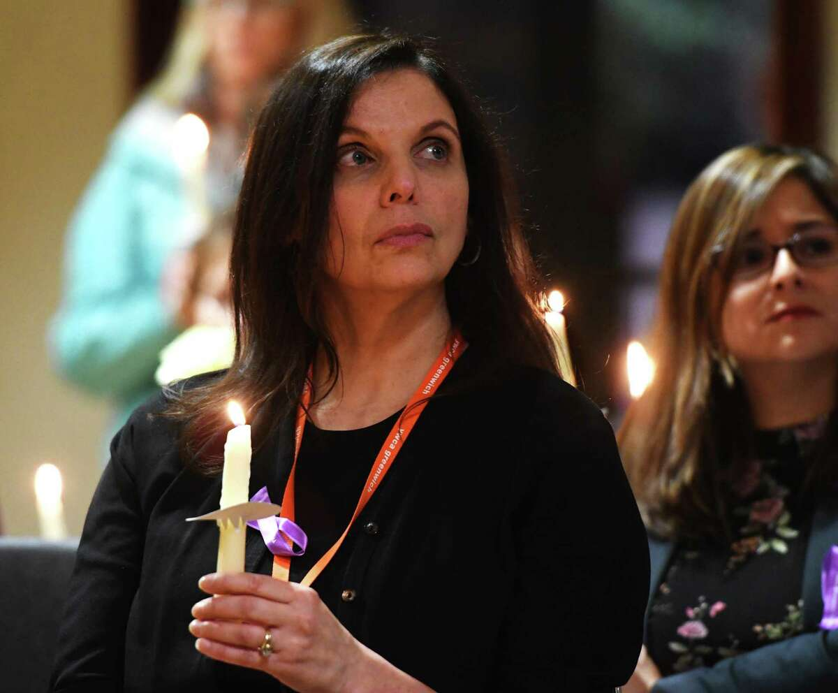 YWCA Domestic Abuse Services Prevention and Outreach Coordinator Leslie Coplin holds a candle at the annual Domestic Violence Candlelight Vigil and Art Show Reception at the YWCA in Greenwich, Conn. Thursday, Oct. 10, 2019. The vigil memorialized those who have lost their lives to domestic violence in the last year, featuring words from a keynote speaker and the presentation of the Purple Ribbon Award to Patrick Mooney for his work in providing free financial literacy counseling to YWCA Greenwich Domestic Abuse Services clients. Artwork created by Domestic Abuse Services clients and staff was on display in the Gertrude White Gallery for viewing after the event and through the end of the month.