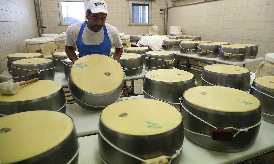 In this photo taken Tuesday, Oct. 8, 2019, Parmigiano Reggiano Parmesan cheese wheels are created in Noceto, near Parma, Italy. U.S. consumers are snapping up Italian Parmesan cheese ahead of an increase in tariffs to take effect next week. The agricultural lobby Coldiretti on Friday, Oct. 11, 2019, said sales of both Parmigiano Reggiano and Grana Padano, aged cheeses defined by their territory of origin, have skyrocketed by 220% since the higher tariffs were announced one week ago. (AP Photo/Antonio Calanni) Photo: Antonio Calanni, Associated Press