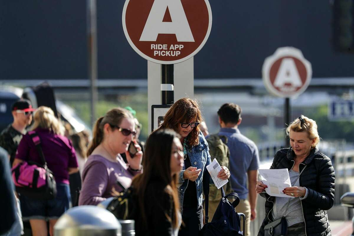 FILE - Present dedicated ride-hailing spot located on LAX departure level is crowded with departing and arriving passengers. Los Angeles International Airport will soon ban ride-hailing companies from picking up passengers outside its terminals. Starting Oct. 29, travelers looking to hop on an Uber or Lyft will be taken by shuttle to a parking lot next to Terminal 1, where they can book their rides.
