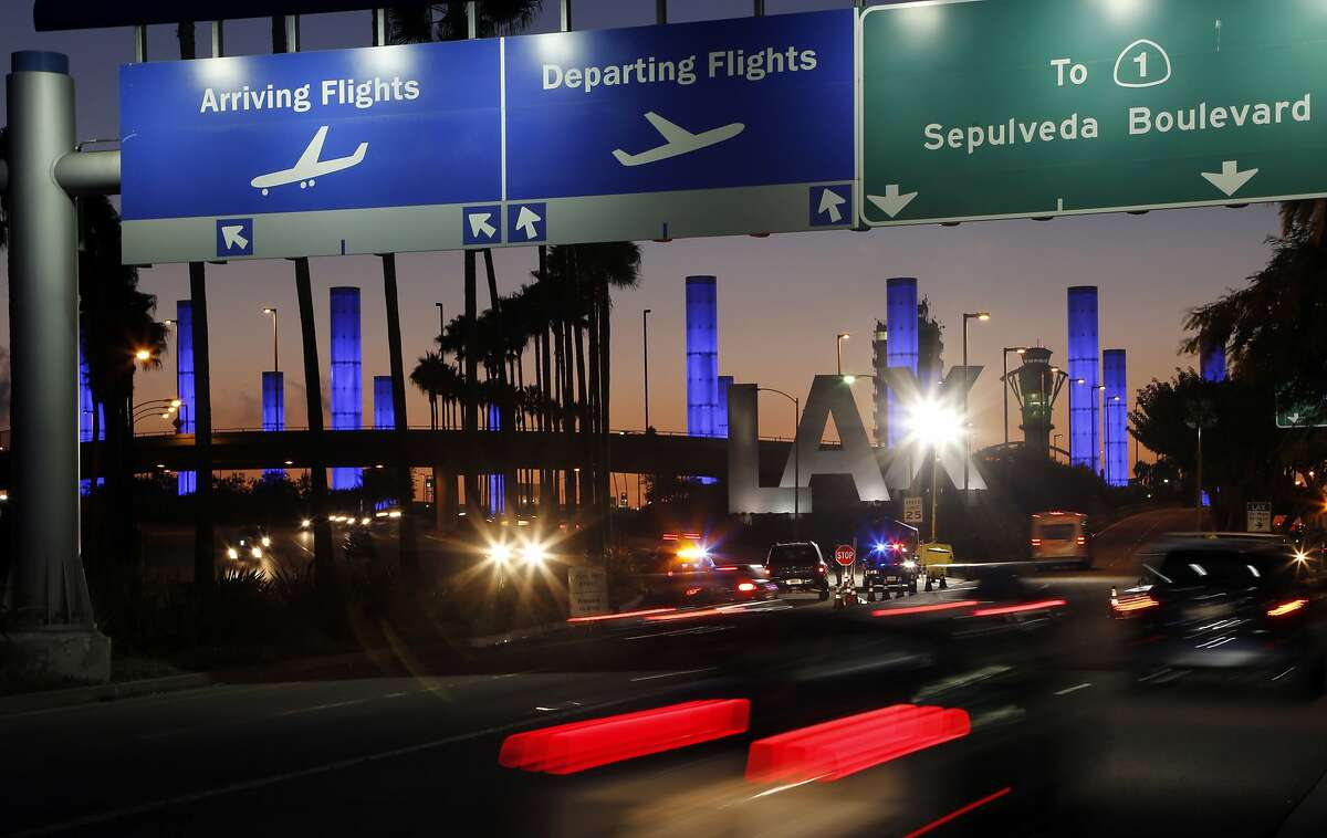 FILE - In this Nov. 2, 2013 file photo lighted pylons line the entrance to Los Angeles International Airport in Los Angeles. On Oct. 29, travelers will not be able to hail a rideshare or taxi outside terminals at Los Angeles International Airport. LAX announced Friday, Oct. 4, 2019, that travelers will instead have to take shuttles or walk to a special location outside the central terminal area where they can be picked up.