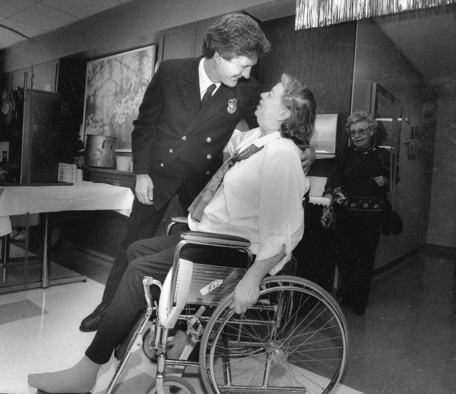 Sherra Cox, after months of treatment for injuries caused by the Loma Prieta quake, is greeted by her rescuer, firefighter Gerry Shannon, at the farewell party held for her by hospital staff. Photo: Michael Maloney / The Chronicle 1989