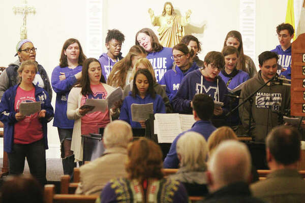 Members of the Marquette High School senior choir perform during the Sixth Annual Walk Against Domestic Violence sponsored by the Alton Police Department Thursday evening. The walk itself was cancelled because of rain, but the program was held at Ss. Peter and Paul Catholic Church.