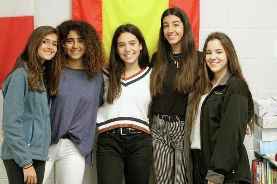 Five Spanish exchange students stand in front of Spain's flag during school late last week.