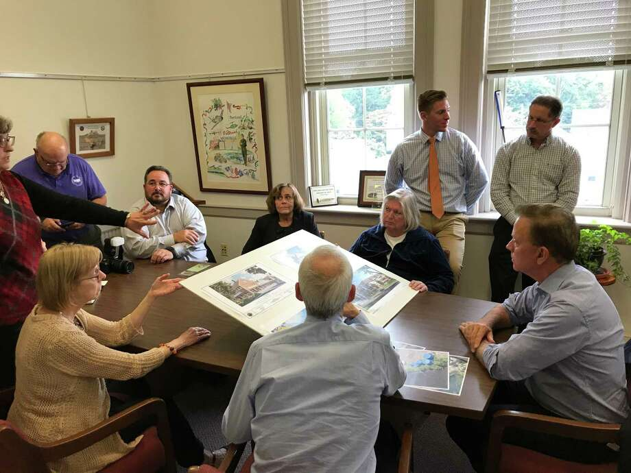 Gov. Ned Lamont and Portland town officials review renderings of Brainerd Place buildings Photo: Jeff Mill / Hearst Connecticut Media