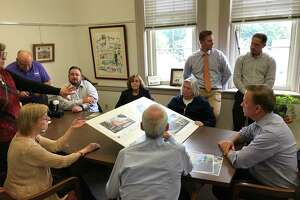 Gov. Ned Lamont and Portland town officials review renderings of Brainerd Place buildings