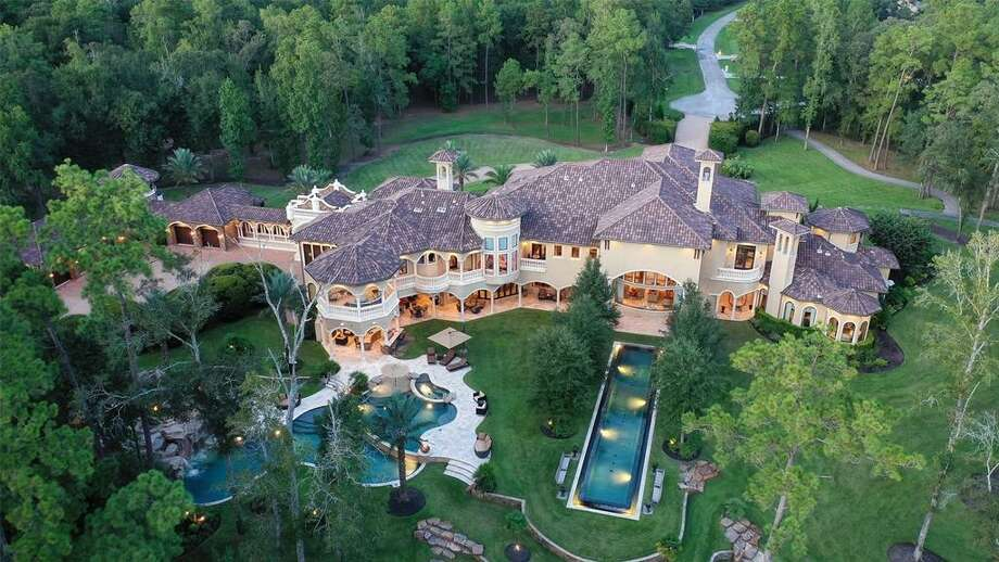 """Situated over nearly 20 acres and boasting more than 14,000 square feet, this $12 million palatial estate in Magnolia is outfitted with stunning amenities such as a climate controlled wine room, custom media room with private balcony, a """"man cave,"""" three pools, in-ground trampoline, private sports court, par-3 golf hole, private pond, large gazebo, outdoor kitchen and more. Photo: Houston Association Of Realtors"""