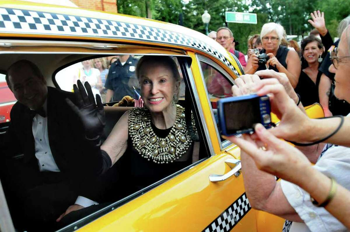 Marylou Whitney, center, waves to her adoring fans as she and husband John Hendrickson, left, arrive in a Taxi for the Whitney Gala at the Canfield Casino on Friday, Aug. 6, 2010, in Saratoga Springs, N.Y. This year's theme is Breakfast at Tiffany's. (Cindy Schultz / Times Union)