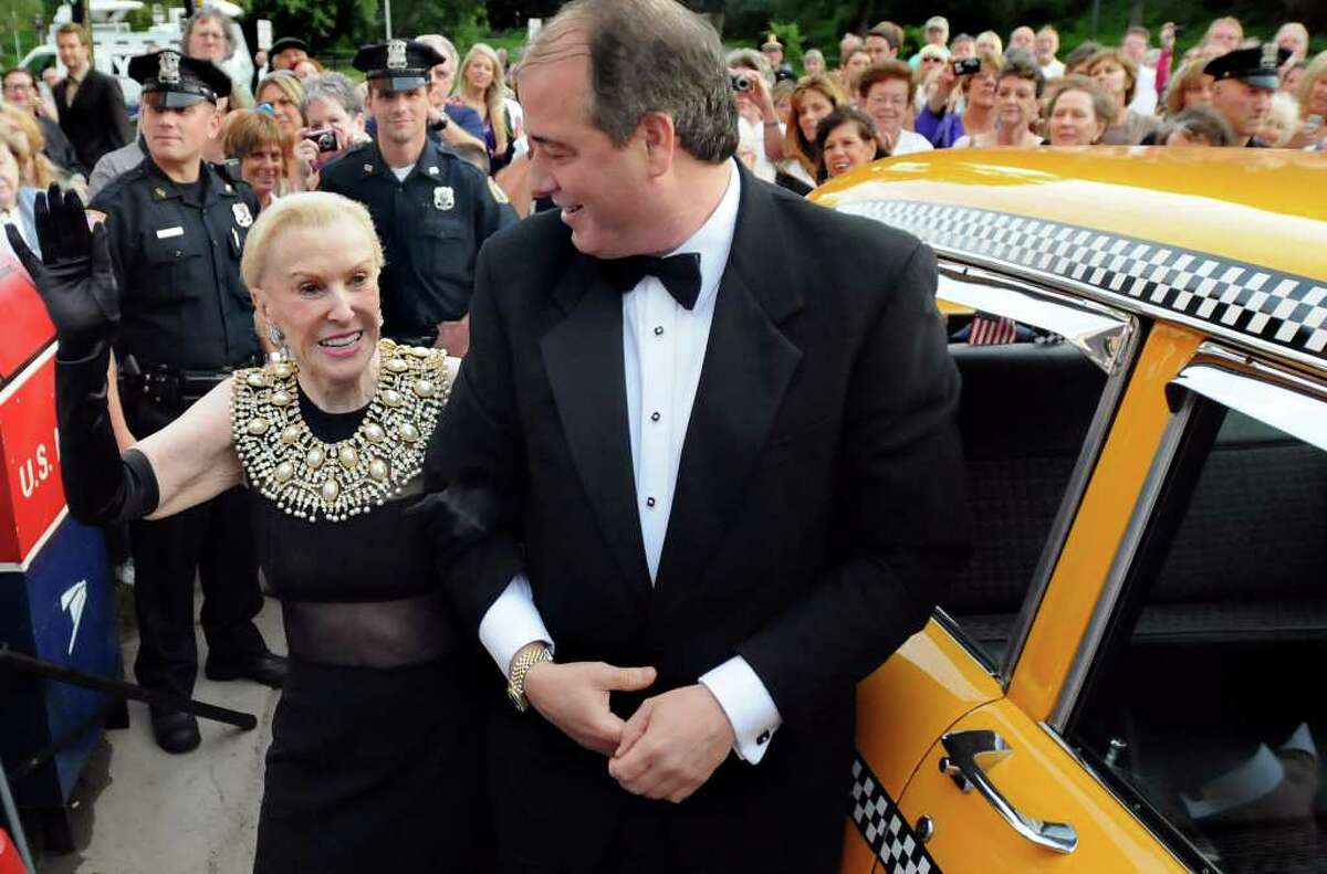Marylou Whitney, left, waves to her adoring fans as and husband John Hendrickson arrive in a Taxi for the Whitney Gala at the Canfield Casino on Friday, Aug. 6, 2010, in Saratoga Springs, N.Y. This year's theme is Breakfast at Tiffany's. (Cindy Schultz / Times Union)