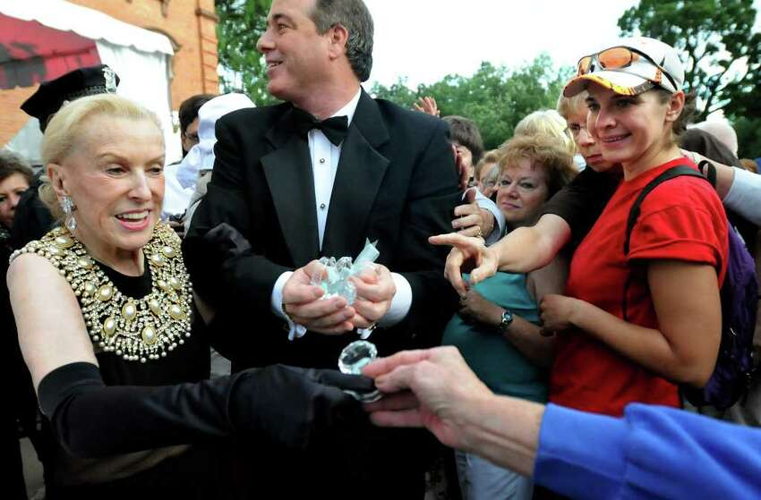 Marylou Whitney, left, and husband John Hendrickson hand out huge faux diamond rings to their fans before the Whitney Gala at the Canfield Casino on Friday, Aug. 6, 2010, in Saratoga Springs, N.Y. This year's theme is