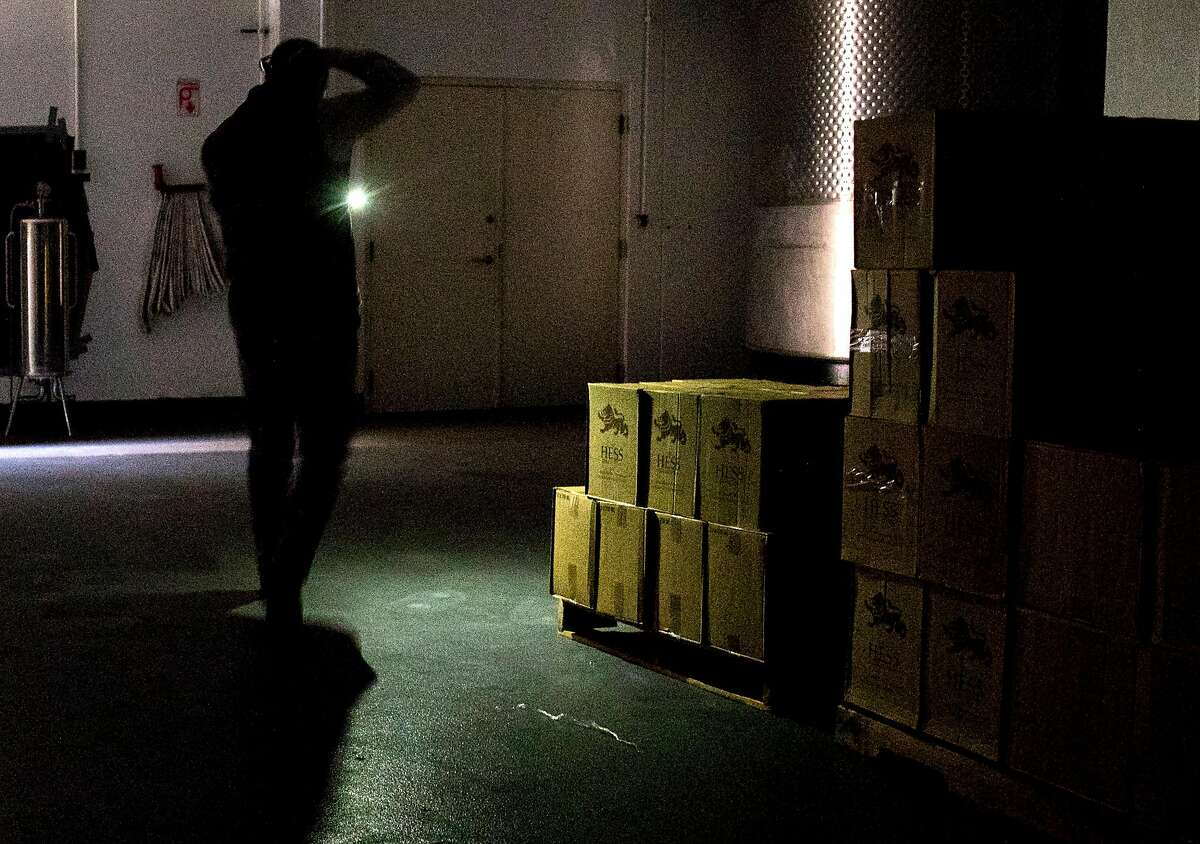 On-site customer director Philip Hansell uses a phone flashlight to navigate through the interior of Hess Winery in Napa, Calif. Thursday, Oct. 10, 2019 after the winery closed due to a PG&E Public Safety Power Shutoffs across Northern California.