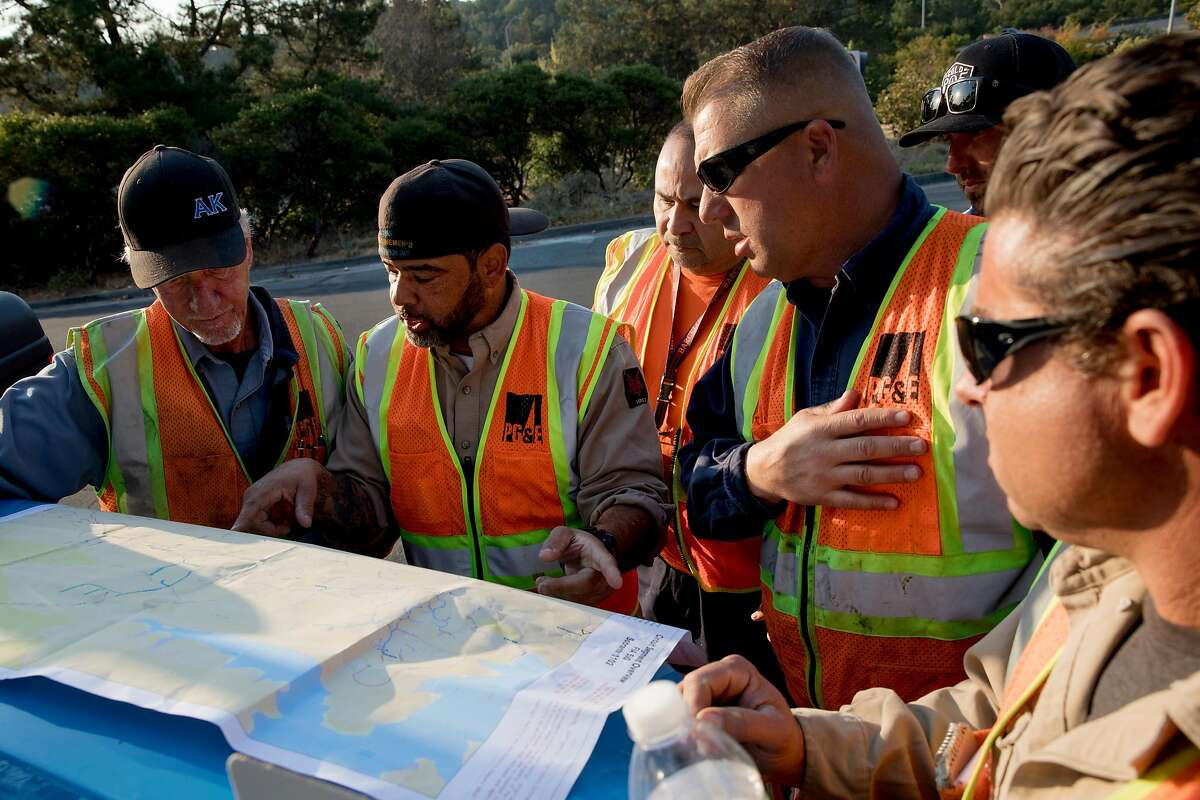 PG&E crews work together to mark off an outage map while observing miles of power lines for damage near El Nido Ranch Road in Lafayette, Calif. Friday, Oct. 11, 2019 following a PG&E Public Safety Power Shutoffs across Northern California.