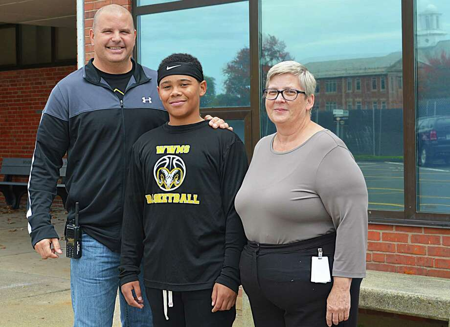 """Woodrow Wilson Middle School assistant principals David J. Mierzejewski, left, and Diane M. Niles, right, stand with eighth-grader Derick Jackson outside the Middletown facility. Administrators regard Derick as a """"rock star"""" for the strides he has made in both math and language arts intervention classes. Two years ago, the 13-year-old dreaded reading, however, since he's participated in the 180 program and increased his confidence in both disciplines, Derick has discovered a love for the written word. Photo: Cassandra Day / Hearst Connecticut Media"""
