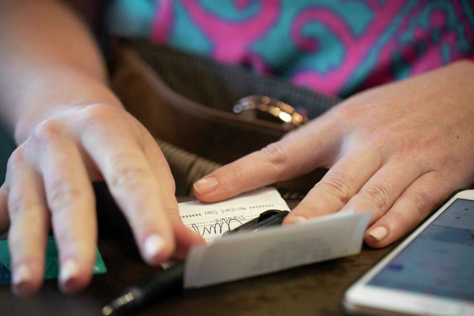 In this Aug. 11, 2019, photo a woman signs a check at a restaurant in New Orleans. Nearly 70% of millennial women have experienced financial abuse by a romantic partner. That means, for every 10 women you know in that age group, odds are that seven of them have had a partner use money to control or manipulate them, according to a 2017 survey of 2,000 people ages 18-35 by CentSai, a financial wellness website. (AP Photo/Jenny Kane)