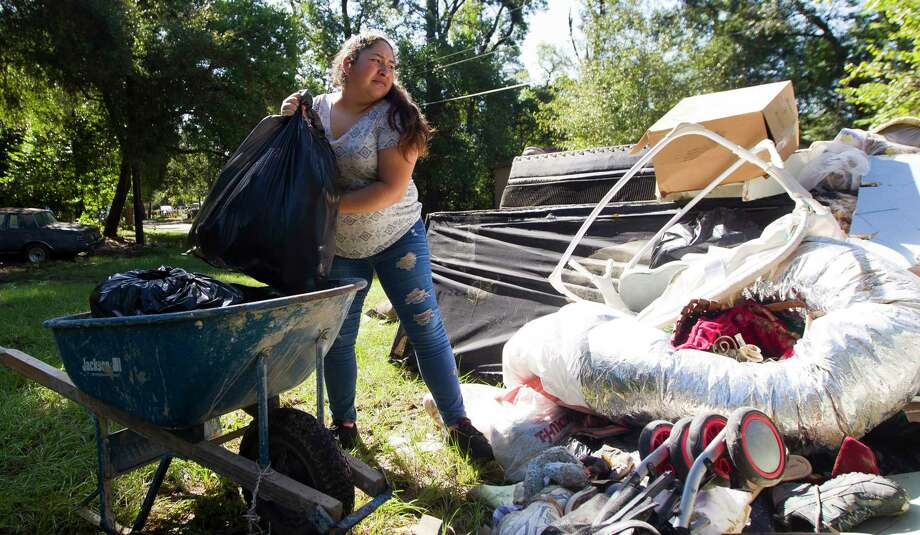 Wendy Ramirez tosses bags of debris from her father's home in the Walden Woods subdivision, Tuesday, Sept. 24, 2019, in New Caney. Photo: Jason Fochtman, Houston Chronicle / Staff Photographer / Houston Chronicle