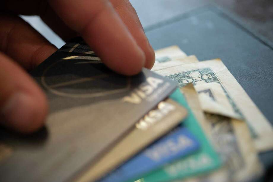 In this Aug. 11, 2019, photo a man puts his Visa card on a stack of cards for a split check at a restaurant in New Orleans. According to a NerdWallet study $35 is the average fee the countrya€™s largest banks charge customers who overdraw their accounts. (AP Photo/Jenny Kane) Photo: Jenny Kane / ap