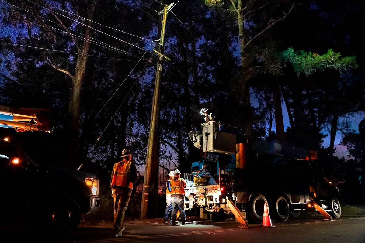A PG&E crew repairs the last of broken power line on Skyline Blvd. before powering it up at 7:30 p.m. on Thursday, Oct. 10, 2019 in Oakland, Calif..