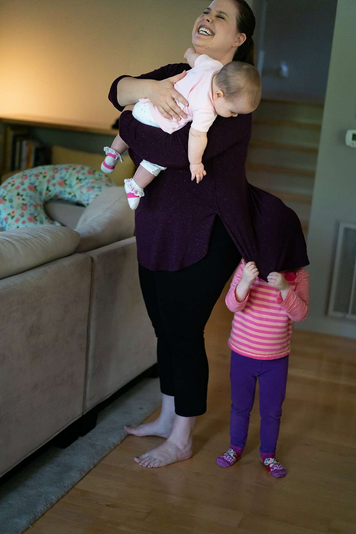 Tilly Gorback, 3, playing peek-a-boo with Cecelia, 7-months, being held by mother, Gennie Gorback on Friday, Oct. 11, 2019 in Orinda, Calif.