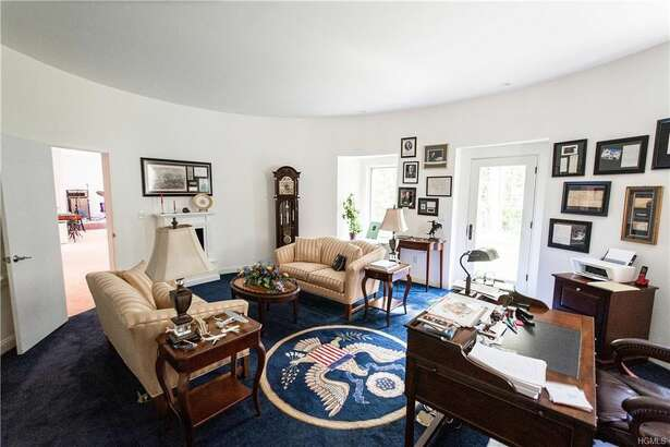 """The interior is tricked-out with a grandfather clock, blue carpet embossed with a presidential seal, gold upholstery, flags, and even a reproduction of """"The Bronco Buster"""" sculpture by Frederic Remington."""