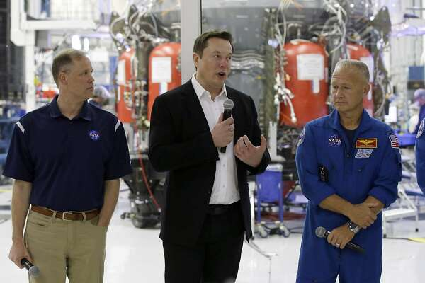 SpaceX founder Elon Musk, center, talks with NASA Administrator Jim Bridenstine, left, and NASA astronauts crew Doug Hurley, right, in front of the Crew Dragon spacecraft, about the progress to fly astronauts to and from the International Space Station, from American soil, as part of the agency's commercial crew program at SpaceX headquarters, in Hawthorne, Calif., Thursday, Oct. 10, 2019. (AP Photo/Alex Gallardo)