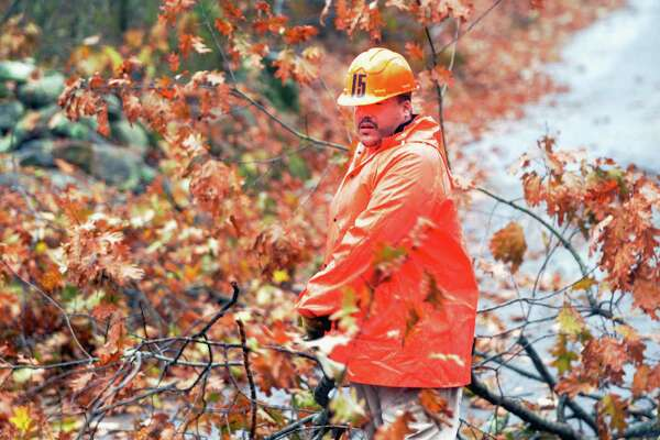 Carlos Velez, an inmate at Willard-Cybulski, in Enfield, Conn. is helping to clear debris from the October Storm along Hampden Road in Stafford, Conn. in 2011. (AP Photo/The Journal Inquirer, Leslloyd F. Alleyne)
