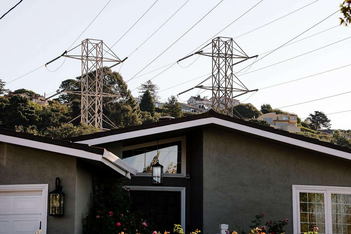 Power lines and towers are seen above homes near the Montclair neighborhood where power is out, in Oakland, California, on Friday, Oct. 10, 2019. PG&E planned power outages affected parts of Oakland and Alameda County as the utility fights to stave off wildfires that can be caused by high winds hitting their power lines.