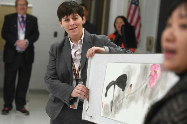 Shelton High Headmaster Beth Smith, left, unfurls a Chinese painting, a gift from Jian Ping High School, Shelton's sister school in Shanghai, China, during a visit by students from the school to Shelton, Conn. on Tuesday, January 29, 2019.